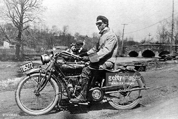 Rakish motorcyclist sitting on bike,1909 Man and woman standing in background