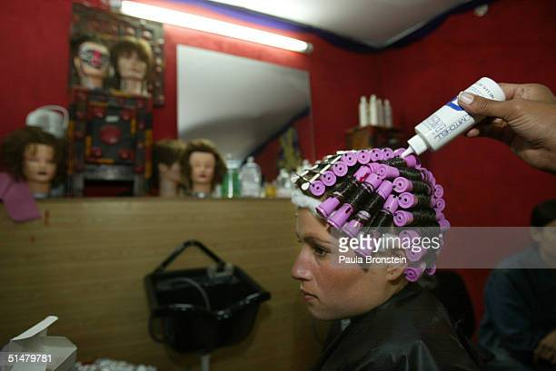 Raksar gets her hair permed by a student beautician during the clinic phase where students train on the public at the Kabul Beauty School on October...
