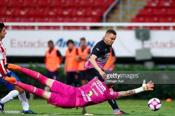 Raúl Gudiño goalkeeper of Chivas fights for the ball with Jonathan Rodríguez of Cruz Azul during the 15th round match between Chivas and Cruz Azul as...
