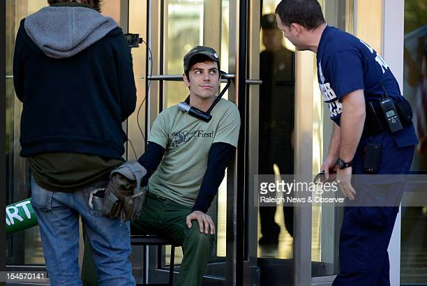 A Raleigh police officer checks on the bicycle lock that protester Mike Bands has used to secure himself to a revolving door at the entrance to the...