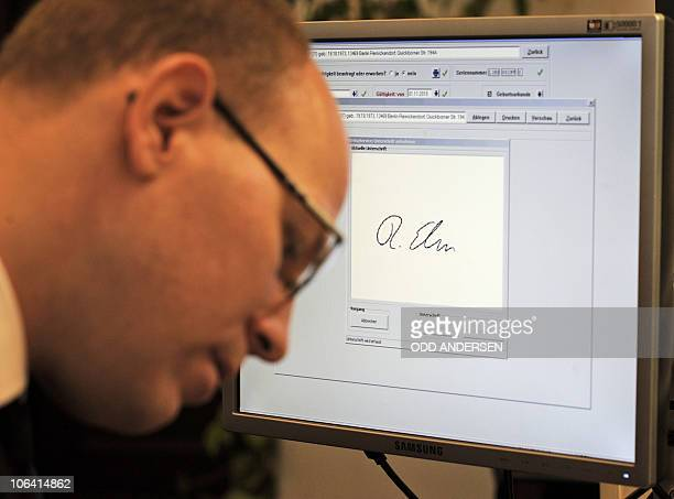 Ralf Ehren's signature is seen on a monitor as he signs on an electronic pad while applying for the new German ID card at the Schoeneberg city hall...