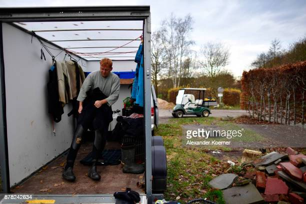 Ralf Oestmann steps into his drysuit before diving for golf balls at a lake at a golf course on November 23 2017 in Achim Germany Oestmann makes a...