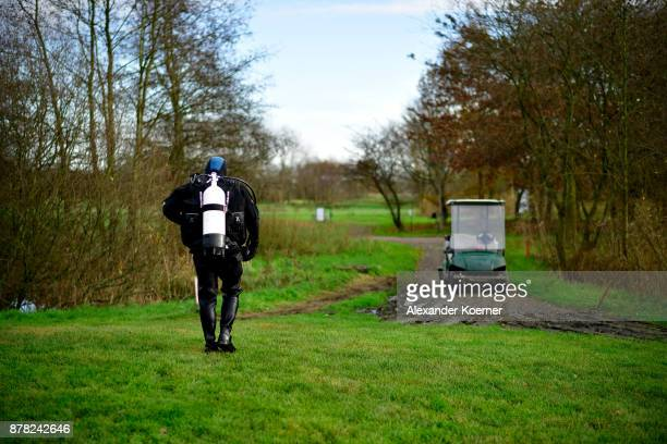 Ralf Oestmann walks in his drysuit towards a golf caddie after recoving golf balls from a lake at a golf course on November 23 2017 in Achim Germany...