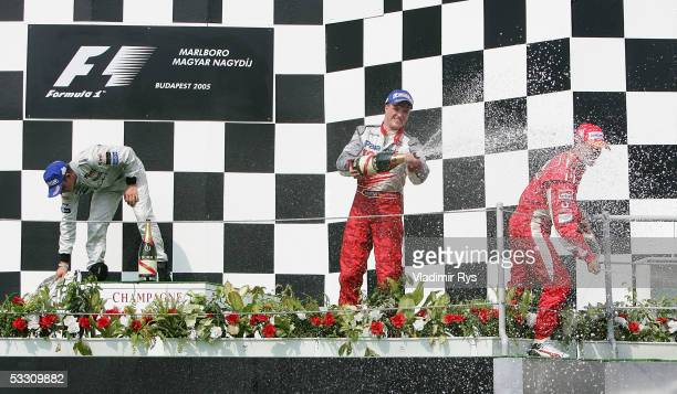Ralf Schumacher of Germany and Toyota and his brother Michael Schumacher of Ferrari celebrate their 3rd and 2nd position while winner Kimi Raikkonen...