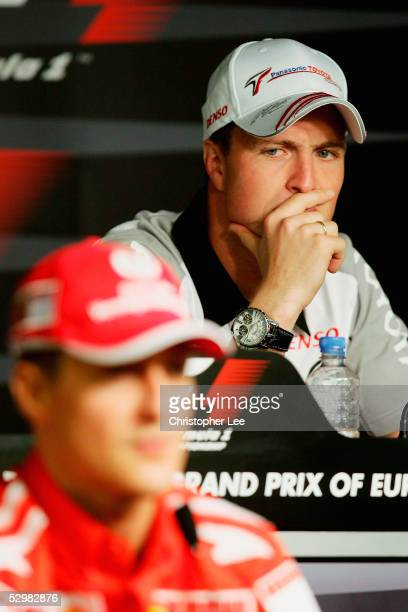 Ralf Schumacher of Toyota looks at his brother Michael Schumacher of Ferrari during the European Formula One Grand Prix Press Conference at the...