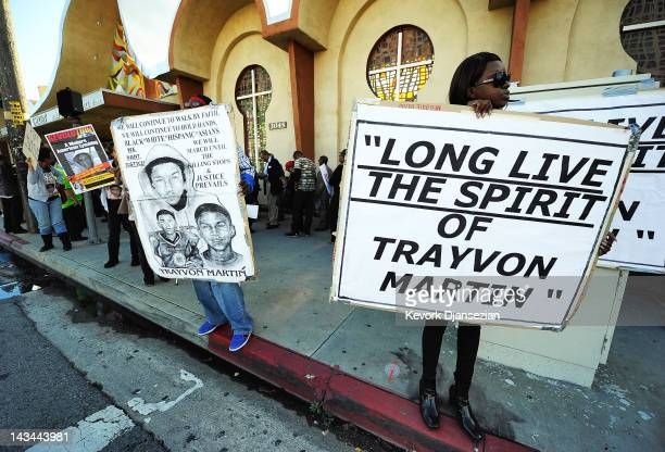 Rally attendees hold signs at the entrance of West Los Angeles Church in Christ during a rally to mark the two-month anniversary of Trayvon Martin's...