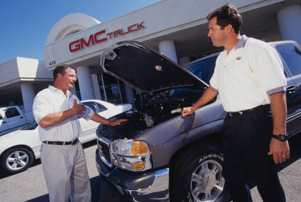 Rally Chevrolet Pontiac Dealership Salesman and Manager Discussing Car