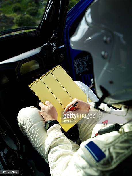 rally co-pilot writeing note - rally car stock photos and pictures