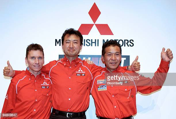 Rally driver Gilles Panizzi left MMSP GmbH President Isao Torii center and rally driver Hiroshi Masuoka pose in front of a Mitsubishi Motors logo at...