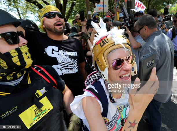 Rally organizer Joey Gibson and rightwing demonstrators react as police fire flashbang grenades at counter demonstrators on the other side of Naito...
