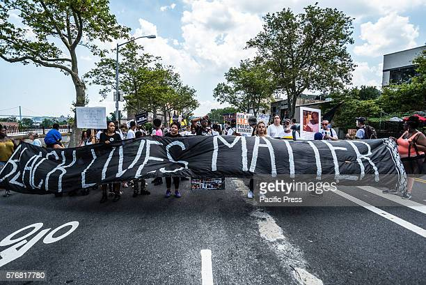 Rally participants hold signs near the site of Eric Garner's death On the second anniversary of the death of Eric Garner during his attempted arrest...
