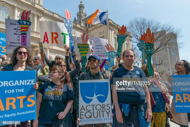 Rally participants hold signs while standing in front of City Hall. Supporters of New York City's cultural institutions and programs held a rally on...
