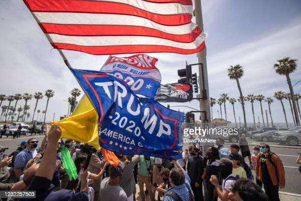 "Rally supporters cary Donald Trump flags at the site of a ""White Lives Matter"" rally on April 11, 2021 in Huntington Beach, California. The rally was..."