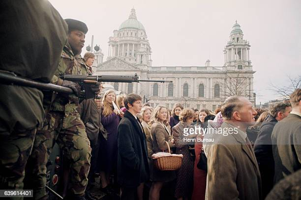 A rally takes place in front of the city hall in the heart of Belfast under the watchful eye of the British military