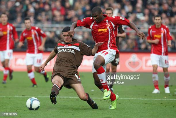 Ralph Gunesch of St. Pauli and Leonard Kweuke of Cottbus battle for the ball during the Second Bundesliga match between FC St. Pauli and Energie...