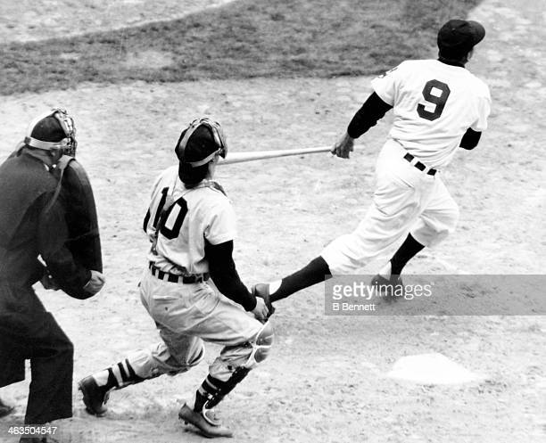 Ralph Kiner of the Cleveland Indians hits his first home run of the season as catcher Sherm Lollar of the Chicago White Sox looks on during their...