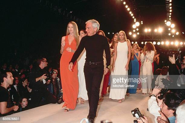Ralph Lauren and Niki Taylor lead a group of models down a runway at a fashion show.