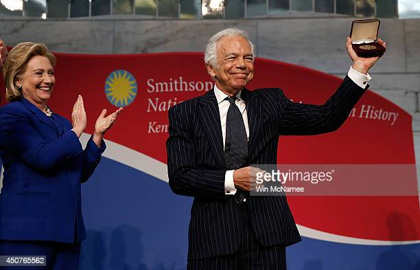 Ralph Lauren holds up the James Smithson Bicentennial Medal after being presented with the award by Hillary Clinton at the National Museum of...
