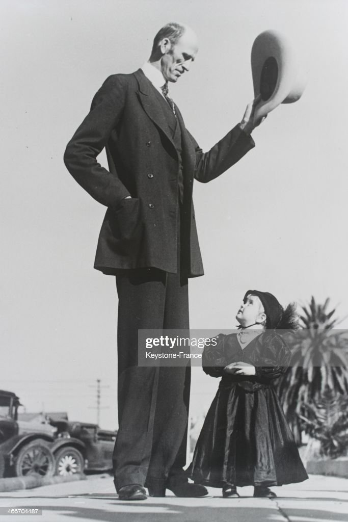Ralph Madsen, nicknamed Tex Madsen, the tallest man in the United States with seven and a half feet height, 228 cm, raises his hat on greeting little Barbara Carlson on July 5, 1932 in Santa Monica, California.