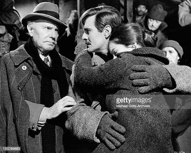 Ralph Richardson tries to console Omar Sharif who's holding Geraldine Chaplin in a scene from the film 'Doctor Zhivago' 1965