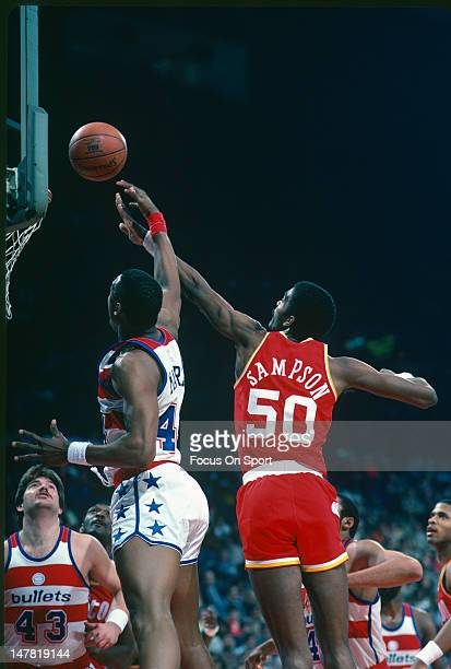 Ralph Sampson of the Houston Rockets battles for a rebound with Rick Mahorn of the Washington Bullets during an NBA basketball game circa 1984 at the...