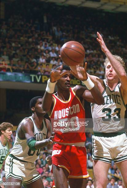 Ralph Sampson of the Houston Rockets passes the ball away from Larry Bird of the Boston Celtics during an NBA basketball game circa 1984 at the...