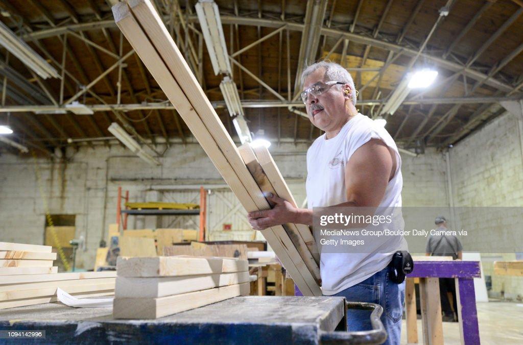 Ralph Soto Sr , shop foreman, picks up precut lumber to