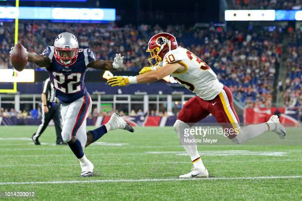 Ralph Webb of the New England Patriots evades a tackle from Troy Apke of the Washington Redskins for a two point conversion during the preseason game...