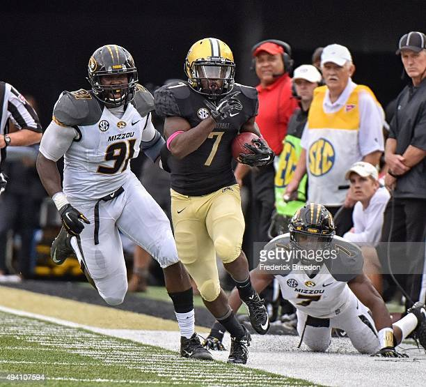 Ralph Webb of the Vanderbilt Commodores carries the ball after making a reception against Charles Harris of the Missouri Tigers during the first half...