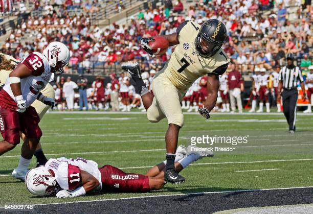 Ralph Webb of the Vanderbilt Commodores jumps over Harvey Harris of the Alabama AM Bulldogs crossing the goal line to score a touchdown during the...