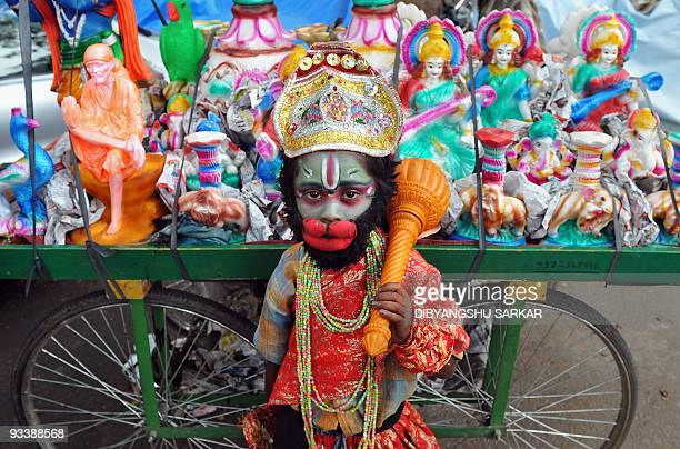 Ram Babu who is dressed as Hindu god Hanuman poses by a cart of idols on the side of a busy road in Bangalore on November 18 2009 Babu dresses like...
