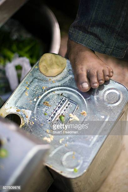 Ram Billas' foot resting on a tin whilst making paratha at Parawthe Wala restaurant in Old Delhi India Gali Paranthe Wali or Paranthe wali Gali means...