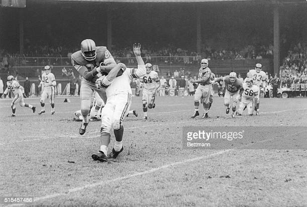 Ram halfback Jon Arnett is stopped by a headlock thrown by Lion Dick 'Night Train' Lane after he gathered in a pass from Zeke Bratkowski during the...