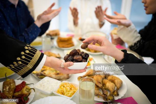 ramadan happiness - breaking fasting and praying together - fasting activity stock pictures, royalty-free photos & images