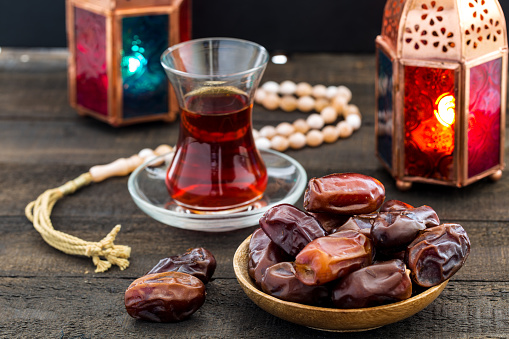 Ramadan Kareem Festive, close up of dates on wooden plate and rosary with oriental Lantern lamps and cup of black tea on wood background. Islamic Holy Month Greeting Card 930726176