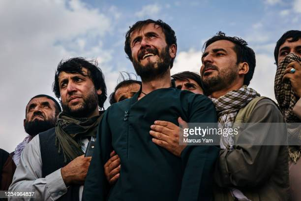 Ramal Ahmadi, center, is supported by family members as he weeps looking up Ð Jet fighters circle the skies above as the U.S. Withdrawal concludes,...