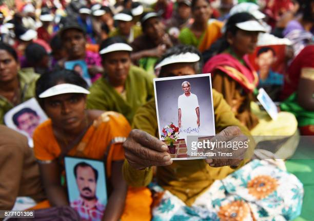 Ramanamma from Andhra Pradesh holding picture of her husband Laxmayya who committed suicide during a demonstration in support of their various long...