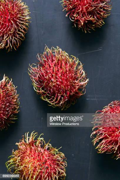 Rambutan (Nephelium lappaceum) fruits on grey surface