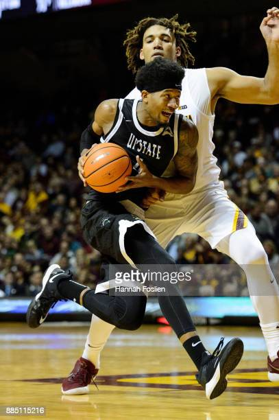 Ramel Thompkins of the USC Upstate Spartans drives to the basket against Reggie Lynch of the Minnesota Golden Gophers during the game on November 10...