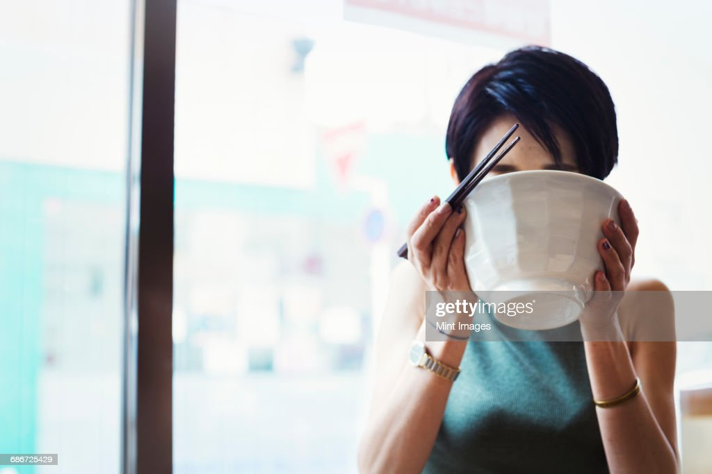 A ramen noodle cafe in a city. A woman seated eating ramen noodle soup, sipping from the bowl.  : Stock Photo
