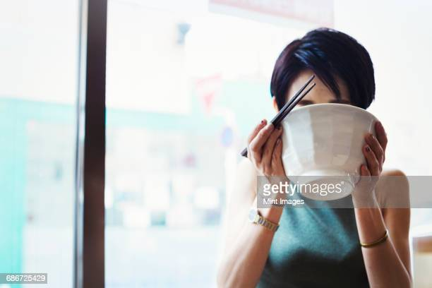 A ramen noodle cafe in a city. A woman seated eating ramen noodle soup, sipping from the bowl.