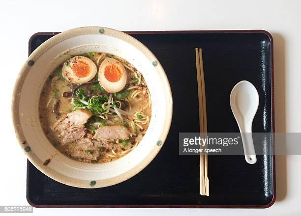 ramen noodles on the black wooden plate with spoon and chopstick - tonkatsu photos et images de collection