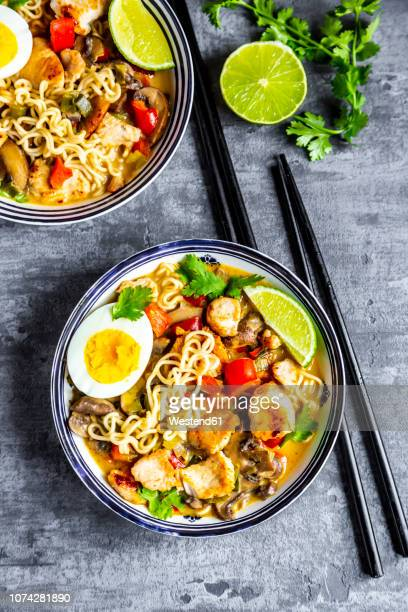 Ramen soup with egg, noodles, chicken meat, paprika, mushroom, spring onion, lime and coriander