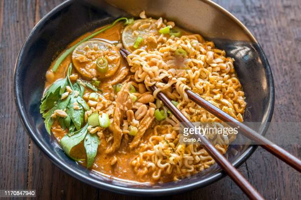 ramen soup with peanut sauce and chicken - ramen noodles stock pictures, royalty-free photos & images