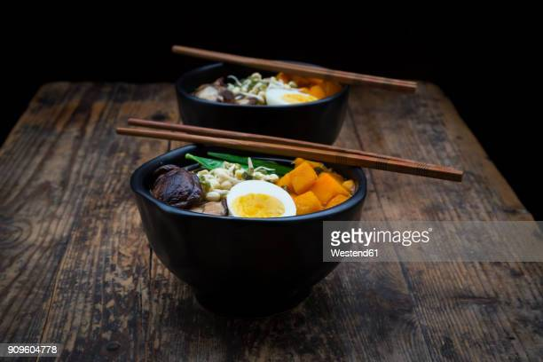 ramen with noodles, egg, hokkaido pumpkin, mung sprout, shitake mushroom in bowl, chopsticks - japanese food stock pictures, royalty-free photos & images