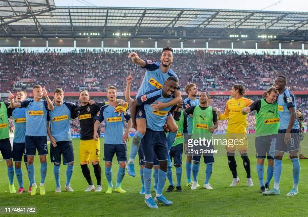 Rami Bensebaini and Marcus Thuram of Borussia Monchengladbach and team mates celebrate victory after the Bundesliga match between 1 FC Koeln and...