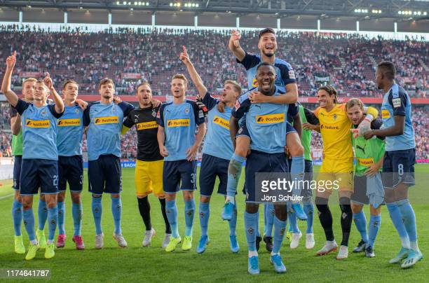 Rami Bensebaini and Marcus Thuram of Borussia Monchengladbach and team mates celebrate victory after the Bundesliga match between 1 FC Koeln and...