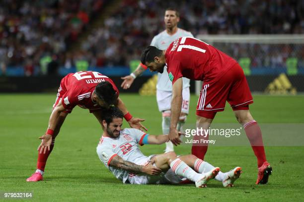 Ramin Rezaeian of Iran and Mehdi Taremi of Iran react to Isco of Spain going down injured during the 2018 FIFA World Cup Russia group B match between...