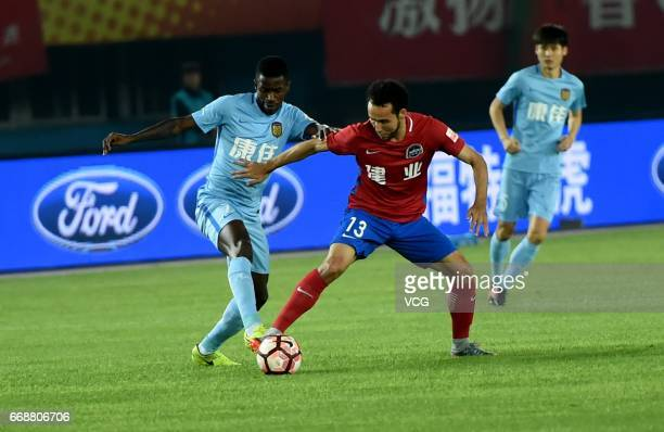 Ramires of Jiangsu Suning and Abduwal Ablet of Henan Jianye compete for the ball during the 5th round match of China Super League between Henan...