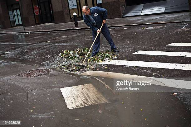 Ramiro Arcos sweeps debris from a storm drain while cleaning up damage caused by Hurricane Sandy on October 30 2012 in the Financial District of New...